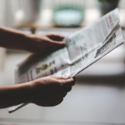 Picture of hands holding a newspapers open