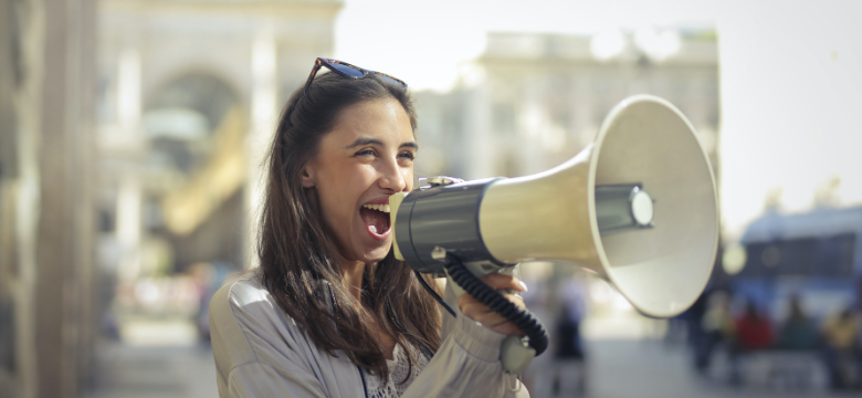 Young woman speaking through a loudspeaker